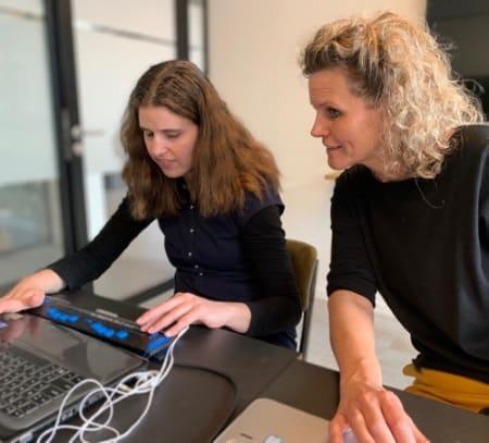 Willemijn achter computer en Angelique kijkt mee